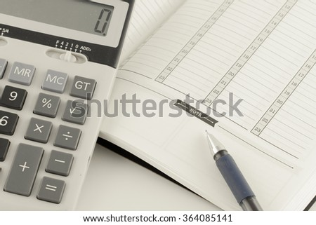 Business concept : Calculator and pen on notebook.
