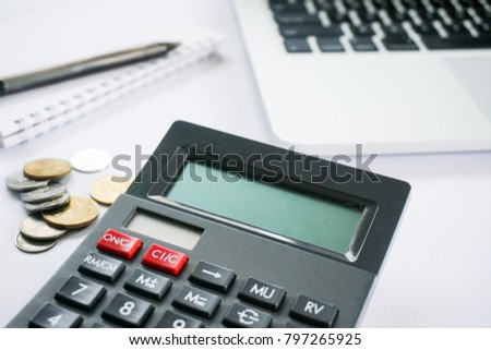 Business concept - Calculator in focus with blurry coins, laptop & notebook as a background