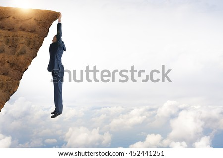 business concept challenge businessman clinging on  - stock photo