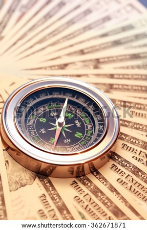 Business concept. Closeup of compass on USA dollar bank notes - stock photo