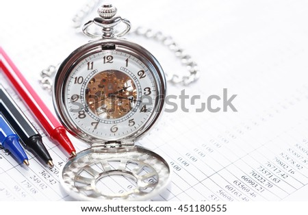 Business concept. Closeup of three colored pens near pocket watch on paper with digits - stock photo