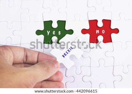 Business Concept - Female hand and missing puzzle with BREXIT YES and no WORD