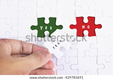 Business Concept - Female hand and missing puzzle with PRAY, YES and no WORD
