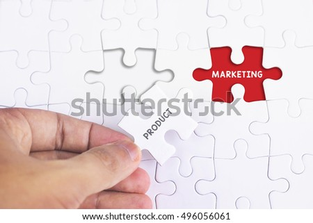 Business Concept - Female hand and missing puzzle with PRODUCT AND MARKETING WORD