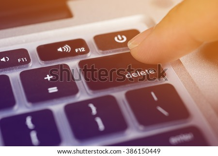 Business concept  finger pressing delete key on  keyboard. - stock photo
