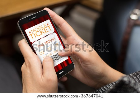 business concept: girl using a digital generated phone with cinema tickets web. All screen graphics are made up. - stock photo
