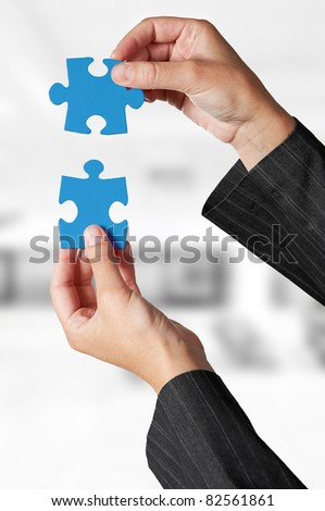Business concept: Hand holding two pieces of a puzzle - stock photo