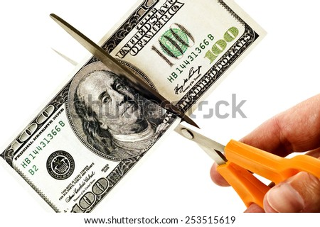 Business Concept Hand Using Scissors To Cut False Hundred Dollar Bill/ Having To Cut Costs - stock photo