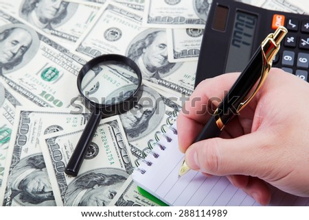 Business concept. Hand with pen and calculator on a background of money. - stock photo