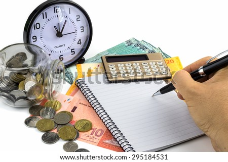Business concept.Hand with pen, calculator, clock and money on white background. - stock photo