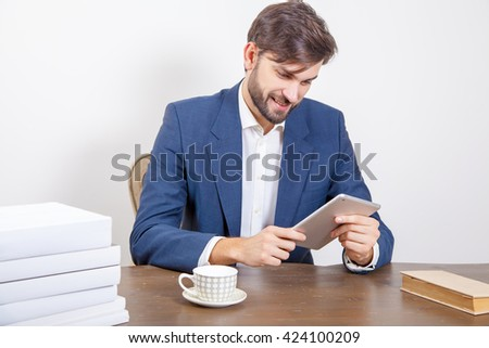 Business concept - handsome man with beard and brown hair and blue suit and tablet pc computer and some books in the office holding tablet and working with smile.  Isolated on white background.   - stock photo