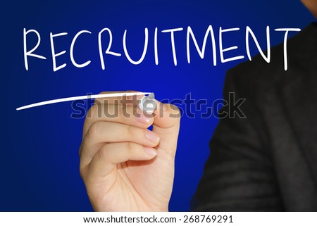 Business concept image of a hand holding marker and write Recruitment over blue background - stock photo