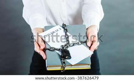 Business concept, limited by contract. Woman holding in hands paper document chained with padlock - stock photo