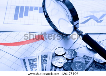 Business concept. Magnifying glass and money on paper background with chart - stock photo