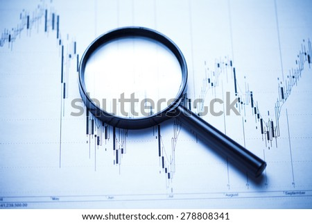 Business concept. Magnifying glass and stock data. - stock photo