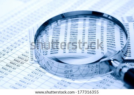 Business concept. Magnifying glass on paper background with digits - stock photo