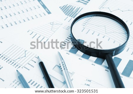 Business concept, magnifying glass pencils and pen on financial charts and graphs - stock photo