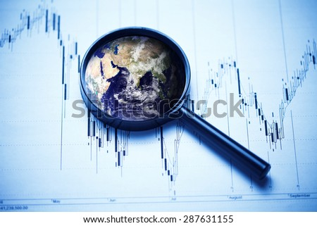 Business concept. Magnifying glass with Earth and stock data. Elements of this image furnished by NASA. - stock photo