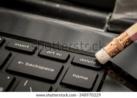 Business concept pencil eraser pointing delete key on keyboard - stock photo