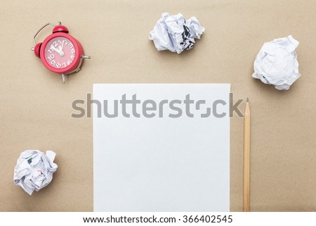 Business concept:red clock,white blank paper,crumpled paper and pencil on brown paper blackground - stock photo
