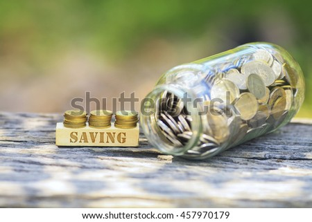 Business Concept - SAVING WORD Golden coin stacked with wooden bar on shallow DOF green background. - stock photo