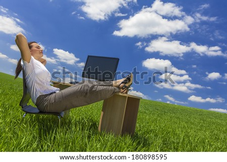 Business concept shot of a beautiful young woman businesswoman relaxing at an office desk & computer in a green field with a bright blue sky & white clouds. - stock photo