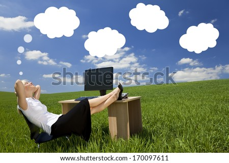Business concept shot of a beautiful young woman relaxing at a desk in a green field day dreaming, white dream clouds in a blue sky.  - stock photo