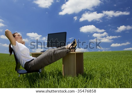 Business concept shot of a beautiful young woman relaxing at a desk in a green field with a bright blue sky. Shot on location. - stock photo