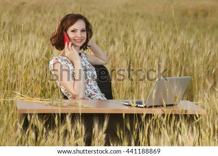 Business concept shot of a beautiful young woman sitting at a desk using a computer in a field. Young businesswoman in sunny meadow nature office.  Young woman with laptop outside. - stock photo