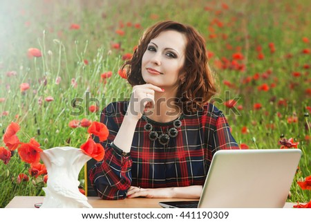 Business concept shot of a beautiful young woman sitting at a desk using a computer in a poppy field. Young businesswoman in sunny poppy nature office. Young woman in red dress with laptop outside. - stock photo