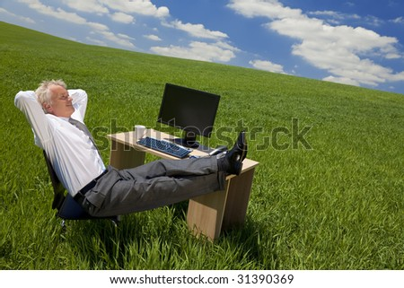 Business concept shot of a businessman relaxing with his feet up on his desk in a green field with a bright blue sky full of fluffy white clouds. Shot on location. - stock photo