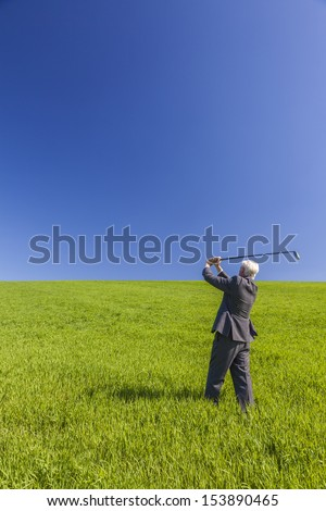 Business concept shot showing an old male man businessman playing golf in a green field with a blue sky. - stock photo