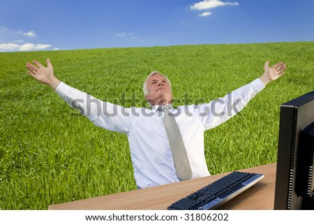 Business concept shot showing an older male executive using a computer in a green field with a blue sky complete with fluffy white clouds. Shot on location not in a studio. - stock photo