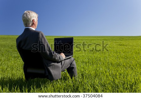 Business concept shot showing an older male executive using a laptop computer in a green field with a blue sky. Shot on location not in a studio. - stock photo