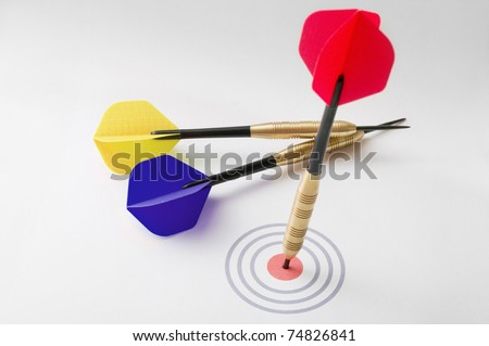 Business concept shot with different colored darts hitting a bullseye. Shallow depth of field. - stock photo