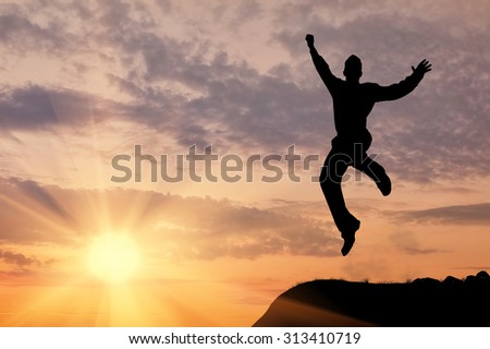 Business concept. Silhouette of a man jumping in the sunset - stock photo