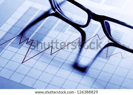 Business concept. Spectacles on paper background with chart - stock photo