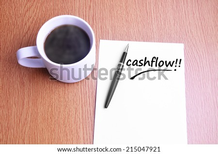 Business Concept - Steamy Coffee And Black Pen With White Paper Writing Cashflow On The Table - stock photo