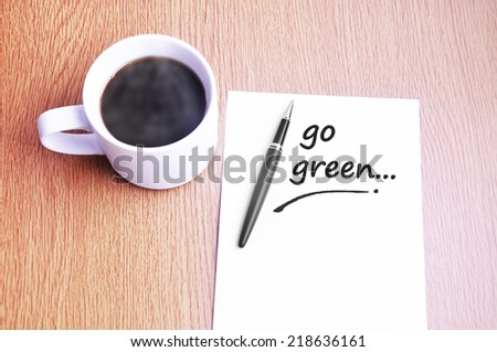 Business Concept - Steamy Coffee And Black Pen With White Paper Writing Go Green On The Table  - stock photo