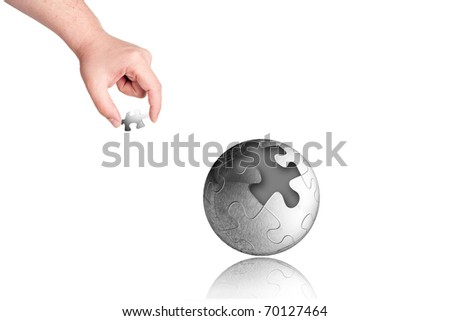 business concept with a hand building puzzle globe on white background with space for text - stock photo