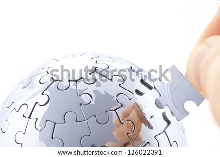 business concept with a hand building puzzle globe on white, space for messages - stock photo