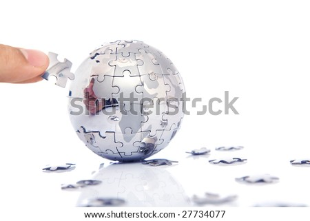 business concept with a hand building puzzle globe on white, space for messages
