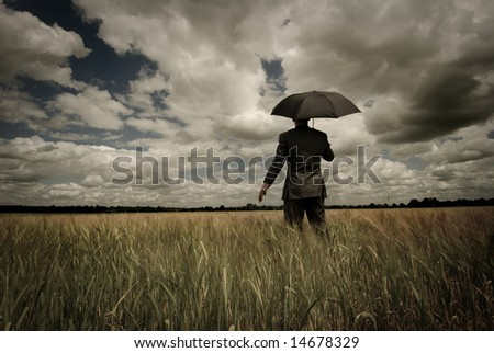 Business concept with a man holding an umbrella as a storm approaches. - stock photo