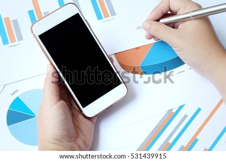 Business concept with documents and mobile phone. Financial accounting stock market graphs analysis.