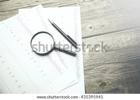 Business concept with magnifier,pen  and financial documents. - stock photo