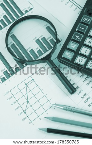 Business concept with magnifying glass, calculator and documents