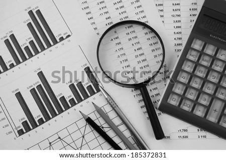 Business concept with magnifying glass, calculator and documents  - stock photo