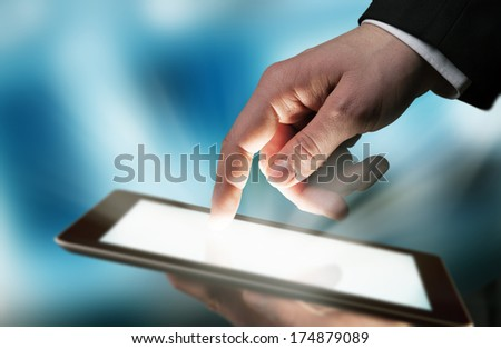 Business concept with man hand touching tablet computer