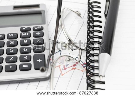 Business concept with notebook, gkasses, pen and calculator - stock photo