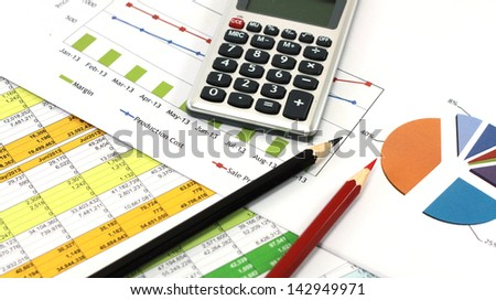 Business concept with pencils, calculator and financial table and graph